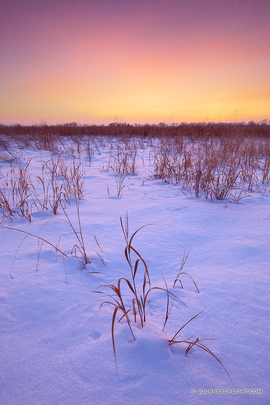 Sunset comes across the cold prairie at Boyer Chute National Wildlife Refuge.  A recent snowfall left a soft, white blanket across the landscape which reflects the warm hues of the setting sun. - Boyer Chute Picture
